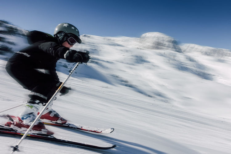 Full length of boy skiing on snow field against sky