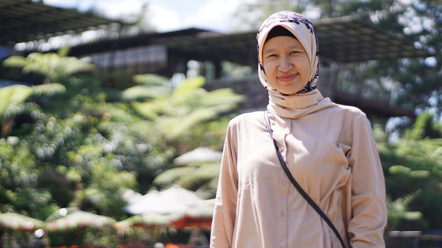 Portrait of woman in hijab standing against plants