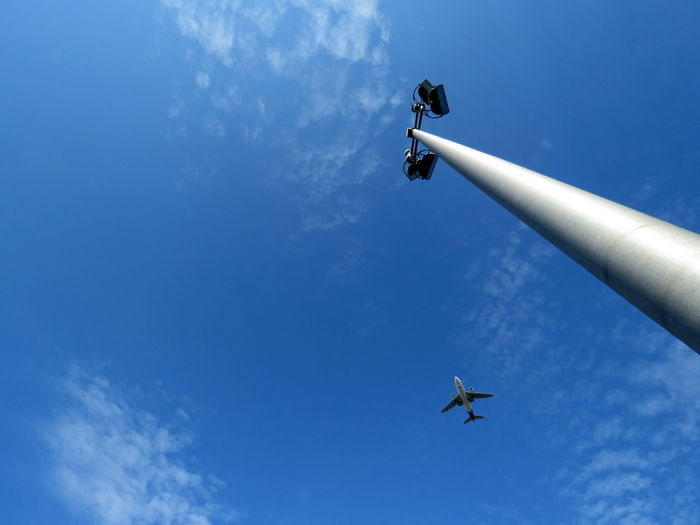 Low Angle View Of Street Light Against Airplane Flying In Sky
