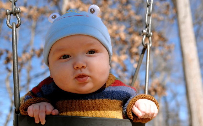 Close-up portrait of baby on swing at playground