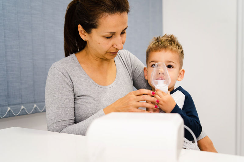 Portrait of mother and son with nebulizer on table