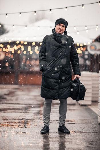 Full length portrait of man standing on street during snowfall