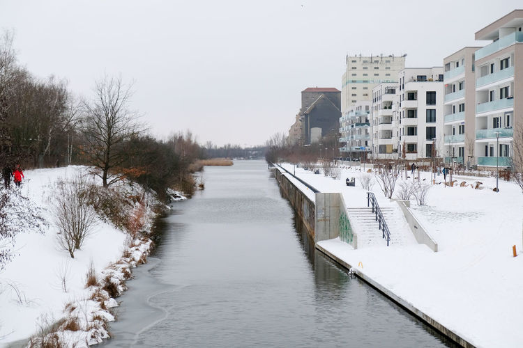 Canal amidst frozen buildings in city against sky
