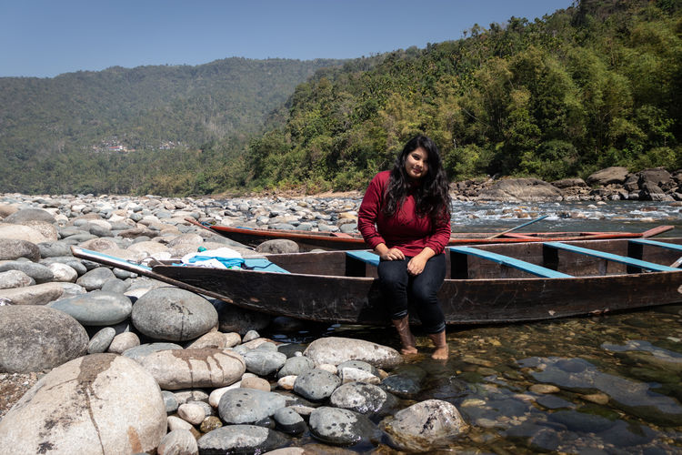 Full length portrait of woman sitting on boat in river