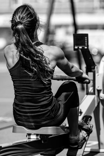 Rear View Of Athlete Exercising On Equipment
