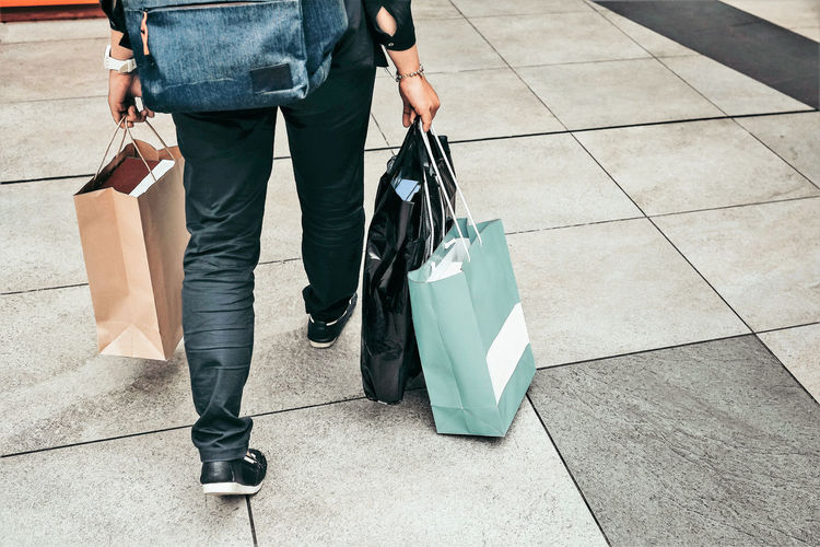 Low Section Of Woman With Shopping Bags Walking On Footpath
