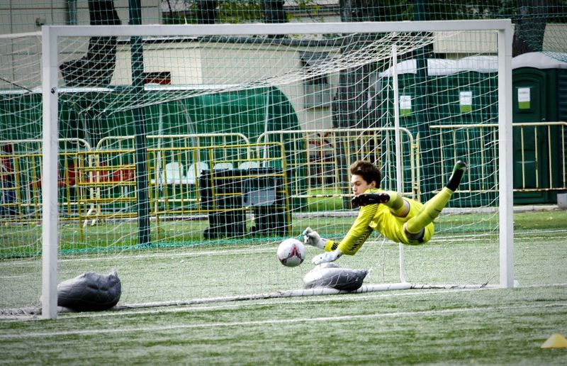 Male goalie playing soccer on field