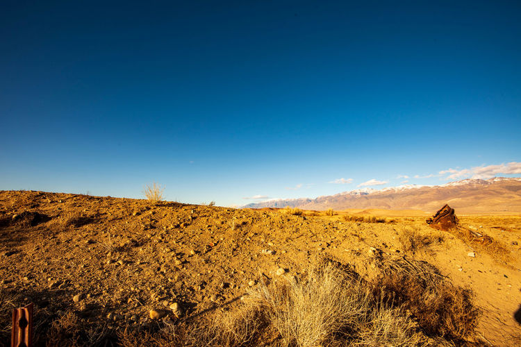 Scenic view of arid landscape against clear blue sky with distant snowy mountains