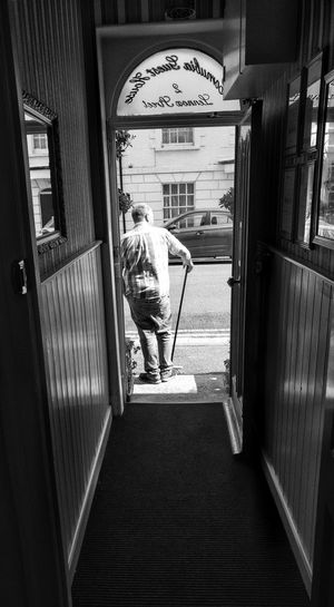 waiting... Weymouth Dorset Adult Adults Only Architecture Black And White Blackandwhite Blackandwhite Photography Built Structure Casual Clothing Day Full Length Indoors  Lifestyles One Person People Real People Rear View Standing Text Walking Women Black And White Friday