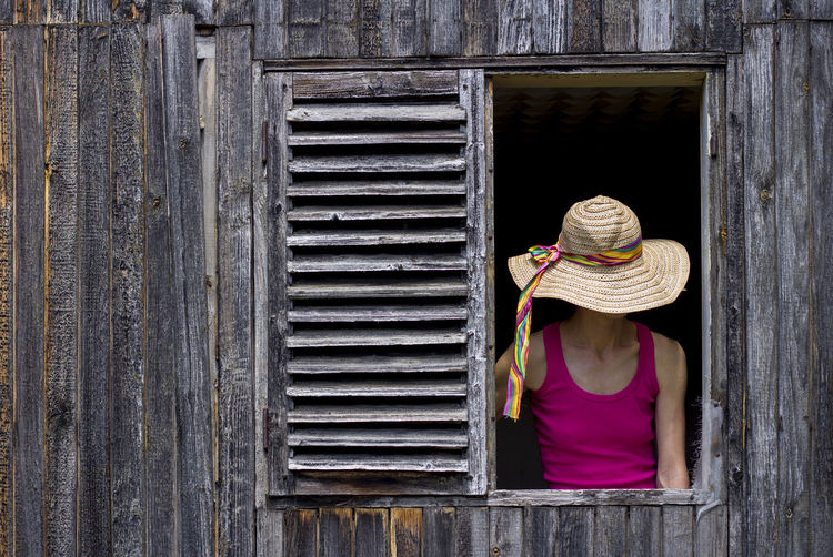 Rear view of woman wearing hat against wall
