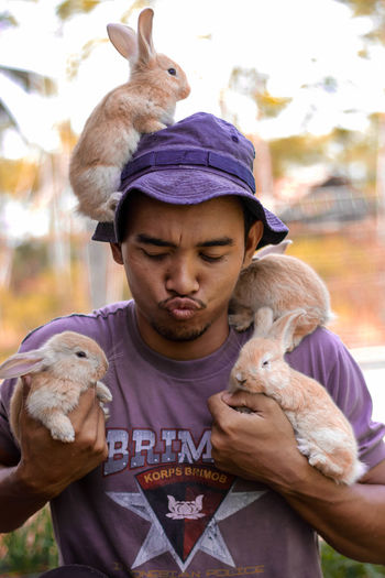 Young Man Puckering While Holding Rabbits