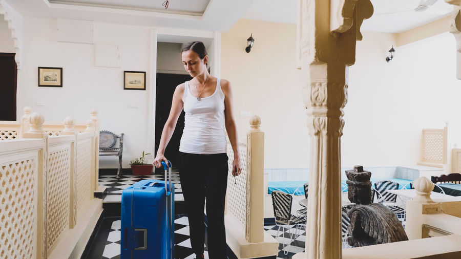 Woman carrying suitcase at hotel