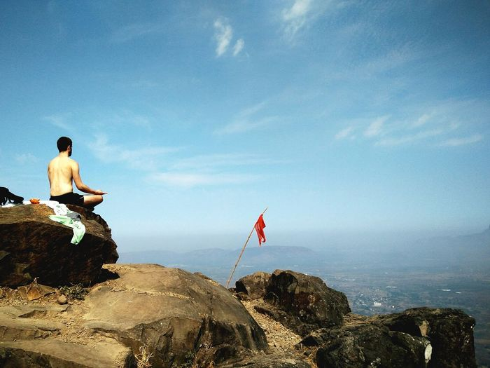 Shirtless Meditating On Rocky Landscape Against Blue Sky