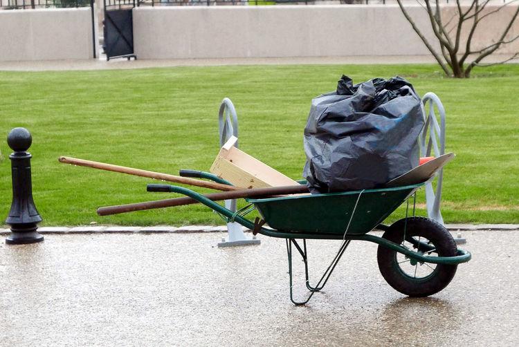 Garbage bag on wheelbarrow against lawn