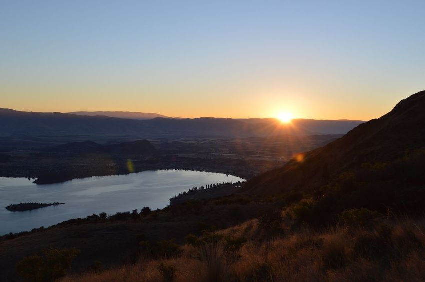Sunrise at Roys Peak Hike Track New Zealand Wanaka Roys Peak Sunrise Sunset Scenics Nature Beauty In Nature Mountain Tranquil Scene Tranquility No People Sun Clear Sky Outdoors Water Sunlight Sky Landscape Travel Destinations Silhouette Mountain Range Day