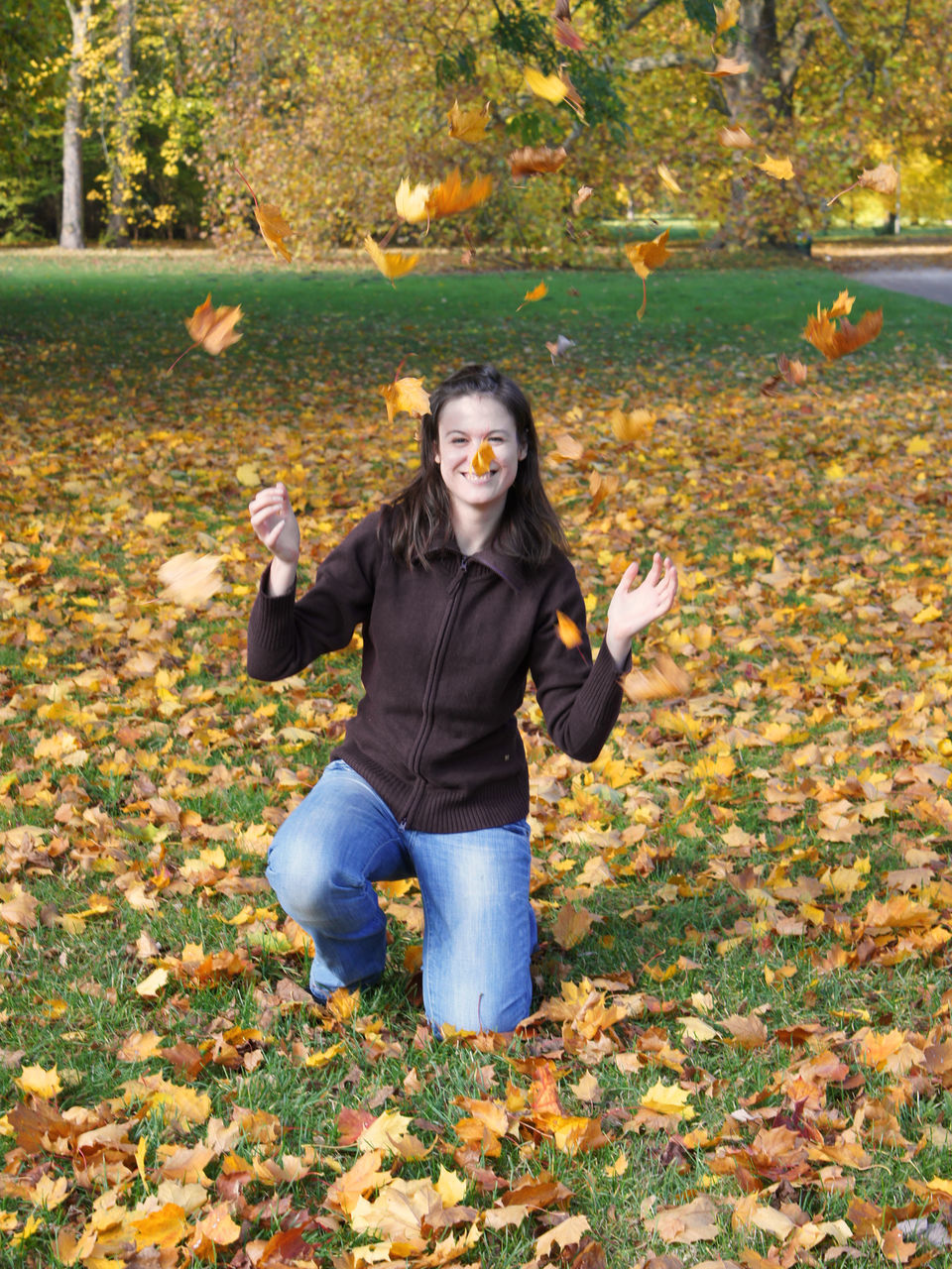 autumn, leaf, looking at camera, change, portrait, front view, standing, outdoors, one person, day, young women, nature, young adult, full length, leisure activity, real people, lifestyles, smiling, tree, happiness, one young woman only, one woman only, adult, people, adults only