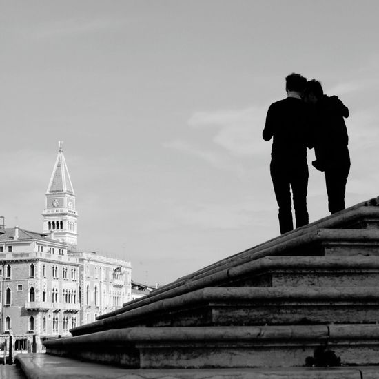 Rear view of couple standing on steps by st mark cathedral against sky