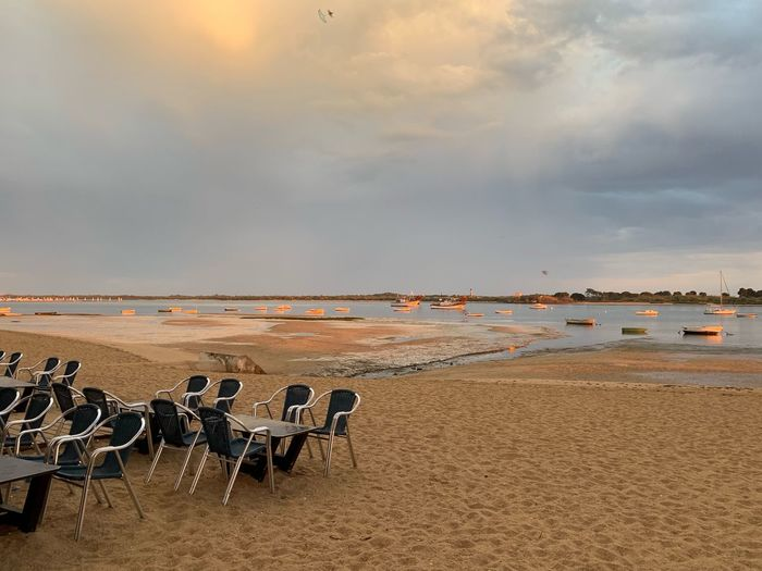 Empty chairs on beach against sky during sunset