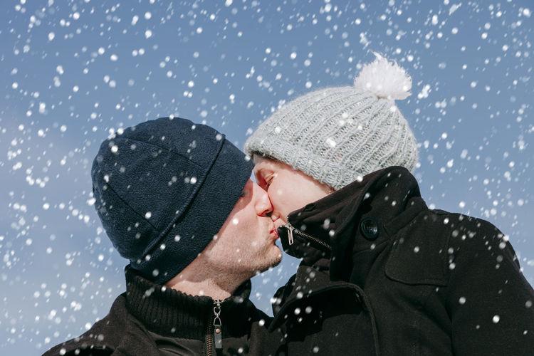 Man kissing woman during winter