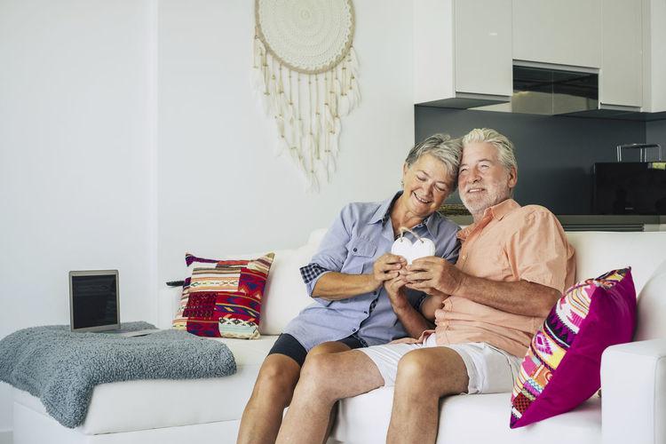 Senior Couple Holding Heart Shape While Sitting On Sofa At Home