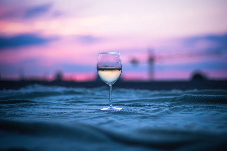 Close-up of drink against sunset sky