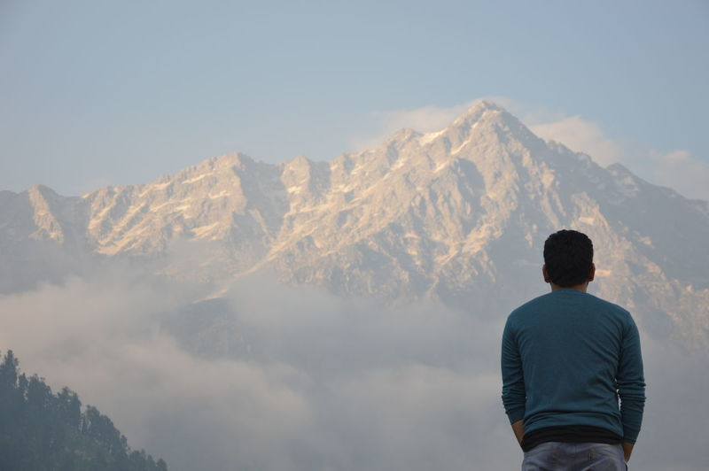Man Standing Against Mountains During Foggy Weather