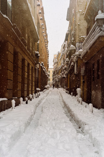 Snow covered alley amidst buildings in city
