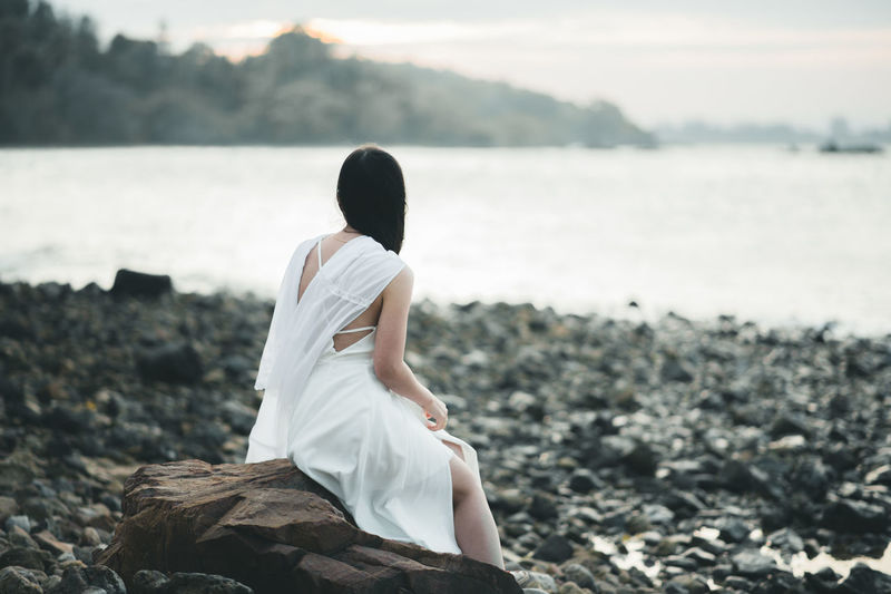 Beach Beauty In Nature Bride Day Focus On Foreground Full Length Leisure Activity Lifestyles Nature One Person Outdoors Real People Rear View Rock - Object Scenics Sea Sitting Sky Standing Water Wedding Dress White Color Women Young Adult Young Women