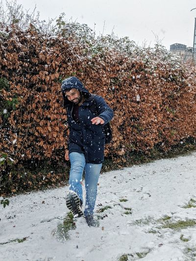 Full length of smiling man playing in snow