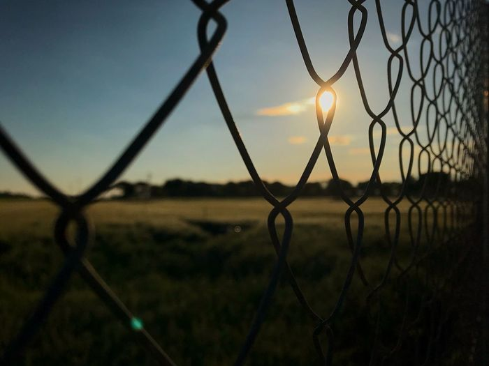 Aprende a vivir encadenado para disfrutar la libertad. Learn to live chained to enjoy freedom. Sunrise Sunset Eye4photography  EyeEmNewHere Landscape EyeEm Best Shots Sky Fence Safety Sunset Protection Security Barrier Boundary Metal No People Field Nature Silhouette Landscape Focus On Foreground