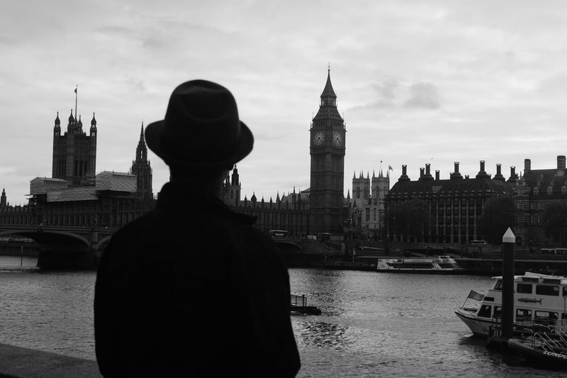 Rear view of man looking at big ben in city against sky