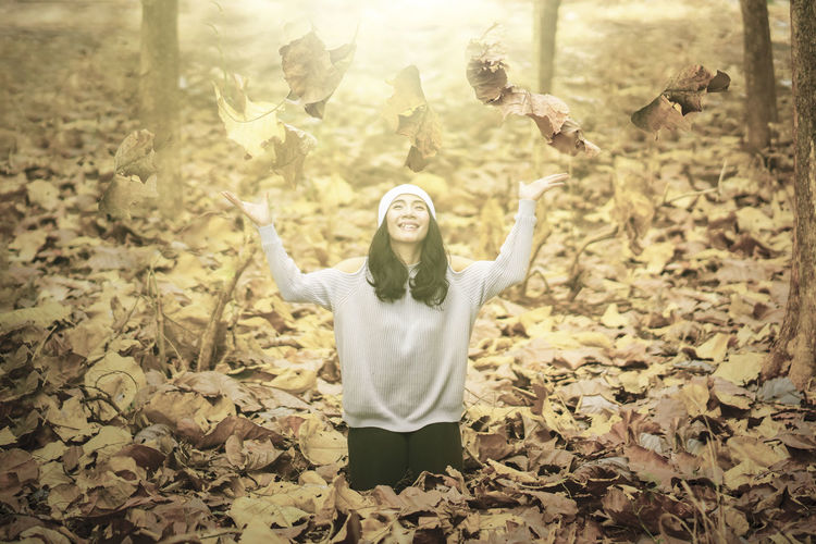 Portrait of young woman with arms outstretched standing on leaves
