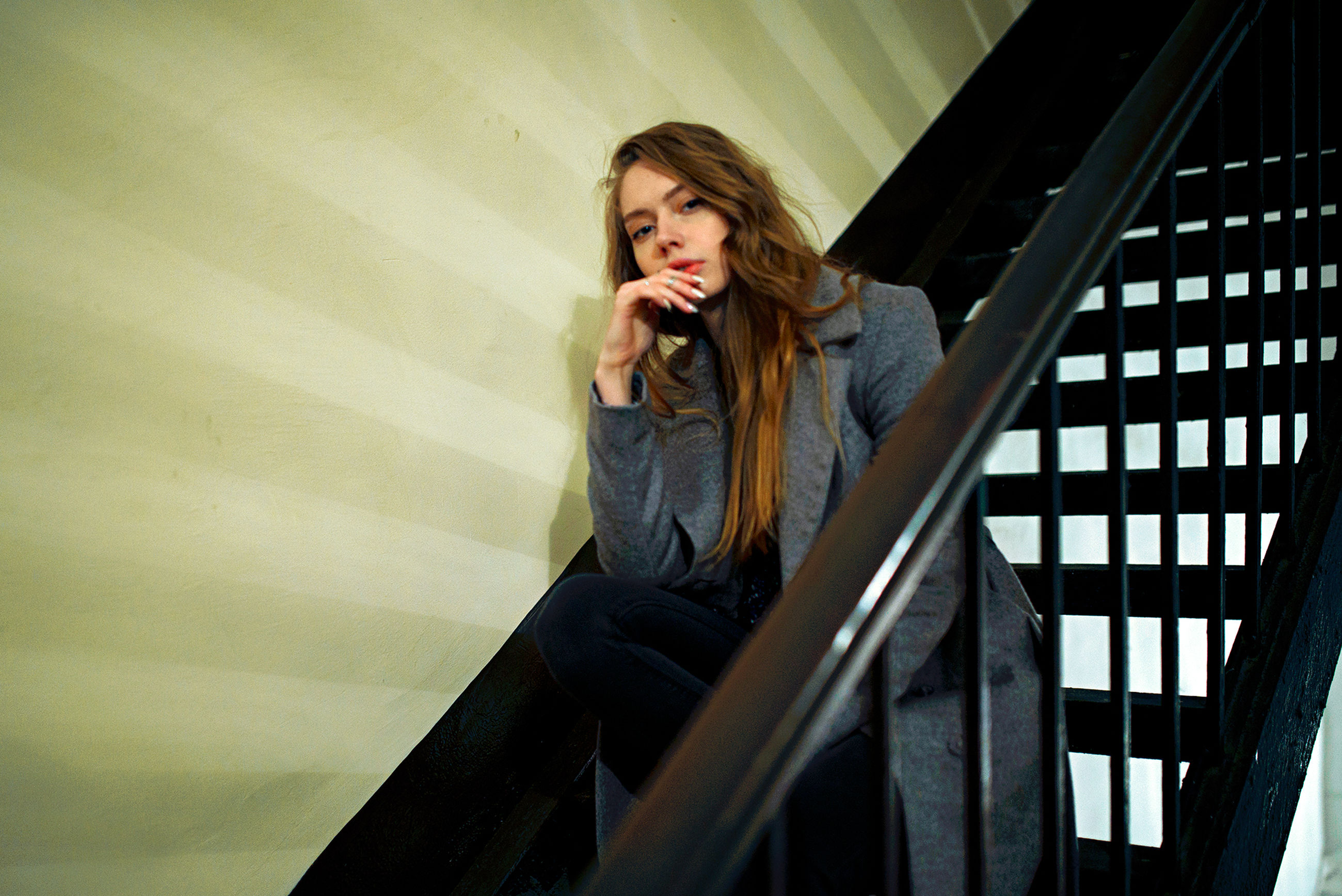one person, real people, young adult, front view, casual clothing, sitting, lifestyles, railing, three quarter length, sadness, young women, contemplation, leisure activity, architecture, staircase, indoors, long hair, emotion, depression - sadness, teenager, hairstyle