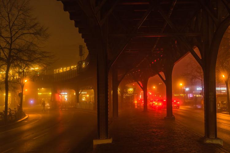 Bridge Over Illuminated Street In City At Night