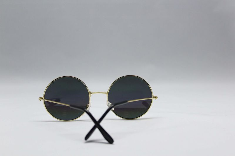 Close-up of sunglasses against sky over white background