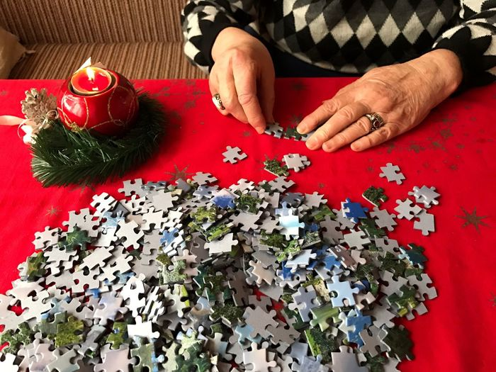 Midsection Of Woman Assembling Jigsaw Puzzle Pieces On Table