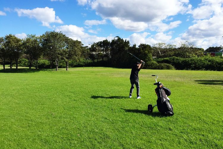Mid adult man playing golf grassy field against cloudy sky during sunny day