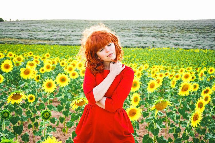 Beautiful woman standing amidst sunflower plants field