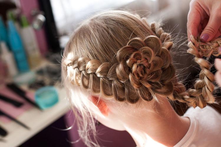 Close-Up Beautician Braiding Hair Of Girl