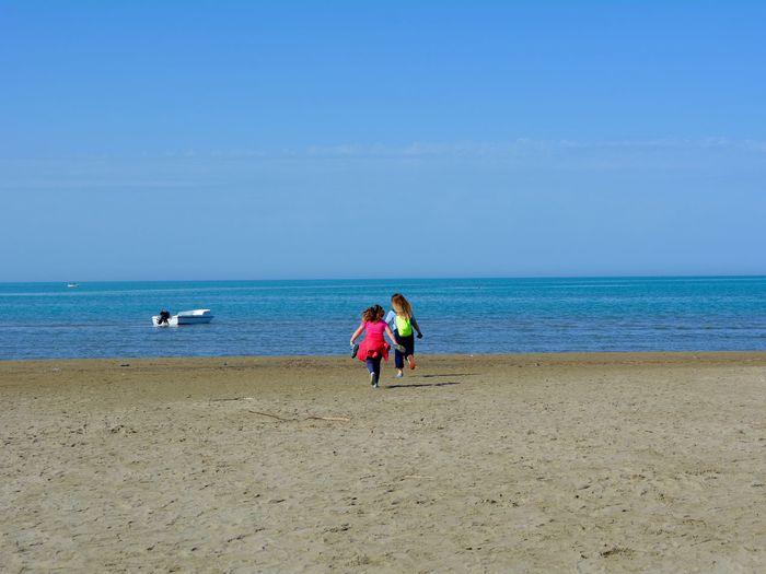 Friends Running At Beach Against Sky