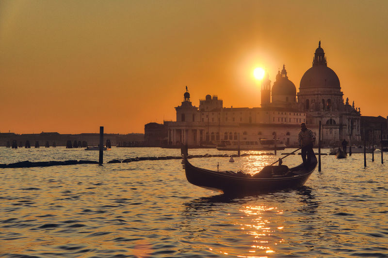 Gondoliere Architecture Building Exterior Built Structure Clear Sky Day Dome Gondola Gondola - Traditional Boat Nature Nautical Vessel Orange Color Outdoors Place Of Worship Real People Religion Sky Spirituality Sun Sunlight Sunset Transportation Travel Destinations Venice Water Waterfront