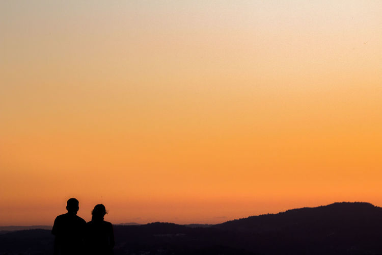 Beauty In Nature Copy Space Couple Couple Shot Lifestyles Love Mountain Nature Orange Color Silhouette Standing Sunset Tranquil Scene Tranquility