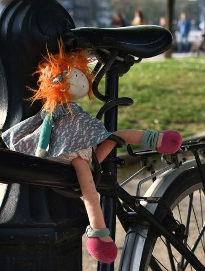 Toy on bicycle by railing