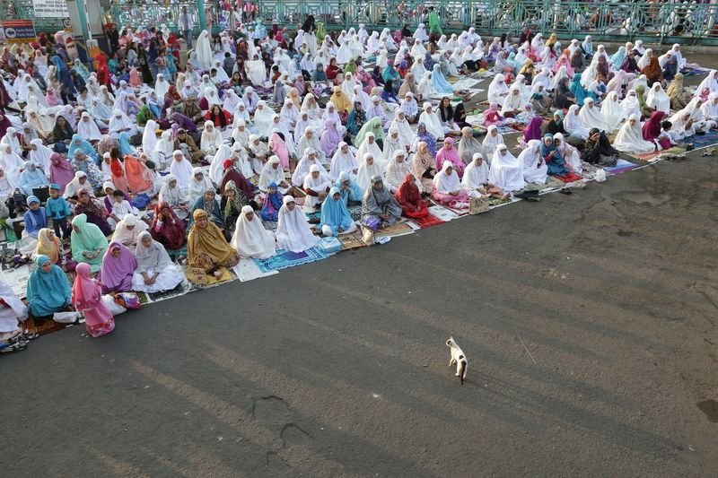 High angle view of woman praying on street during eid-ul-fitr