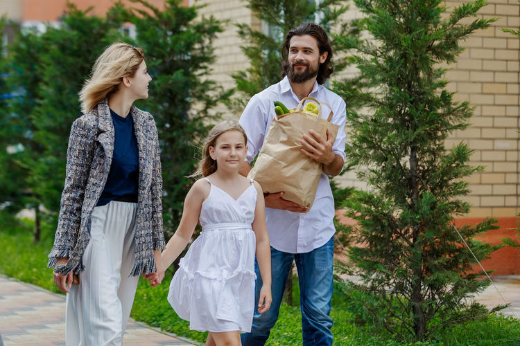 Man holding shopping bag by woman and girl while walking on footpath against plants