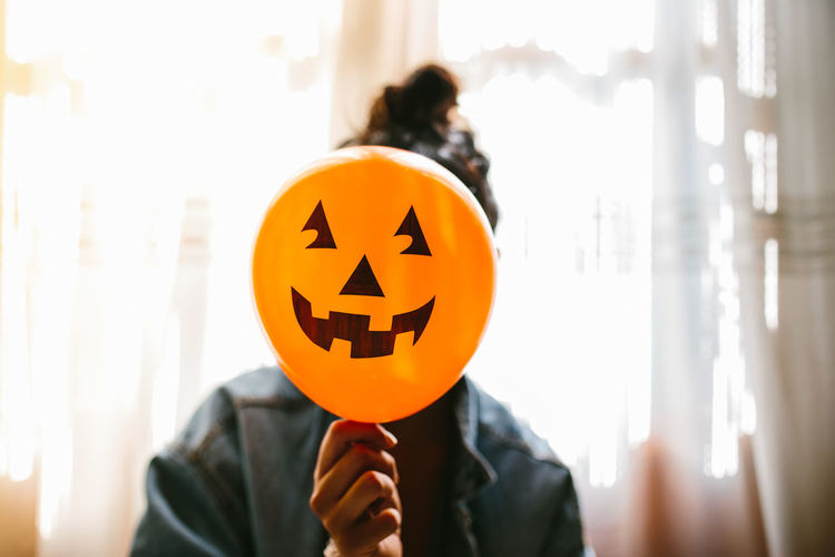 Close-up of woman holding halloween decoration against face at home