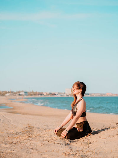 Side view of young woman doing yoga at beach against sky