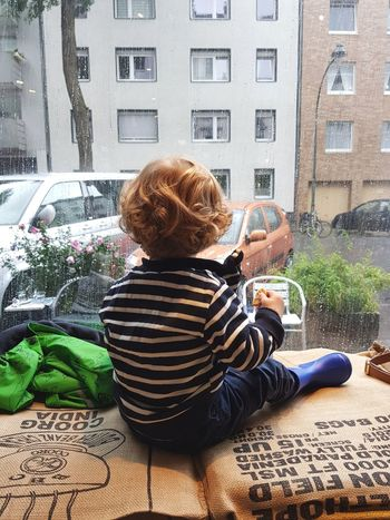 Rainy summer Real People Window Built Structure Indoors  Architecture Day Sitting Childhood Looking Through Window Outdoors Car Blurred Indoors  One Boy Only Reflection Growing Up Toddler  Boy Raindrops Rain Wet Water Puddles City Curly Hair Stories From The City