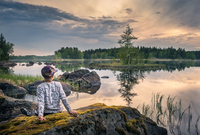 Boy sitting on the stone at scenic summer lake landscape in National Park, Finland Beauty In Nature Childhood Cloud - Sky Finland Holiday Island Lake Leisure Activity Lifestyles National Park Nature Night One Person Outdoors Peaceful People Real People Reflection Relaxing Rock - Object Scenics Sky Summer Sunset Tree Breathing Space Lost In The Landscape