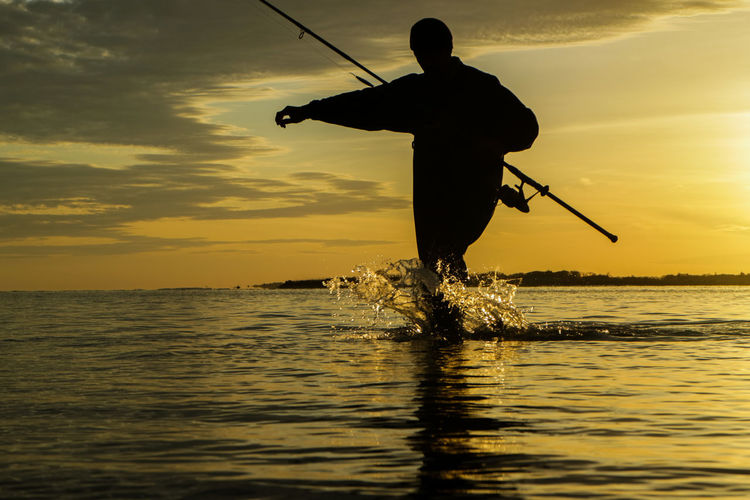 Low angle view of silhouette man with fishing rod in sea during sunset
